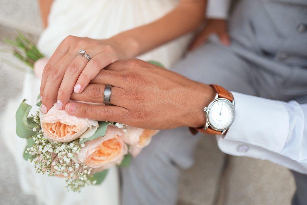 Comunione o separazione dei beni, mani degli sposi su un bouquet