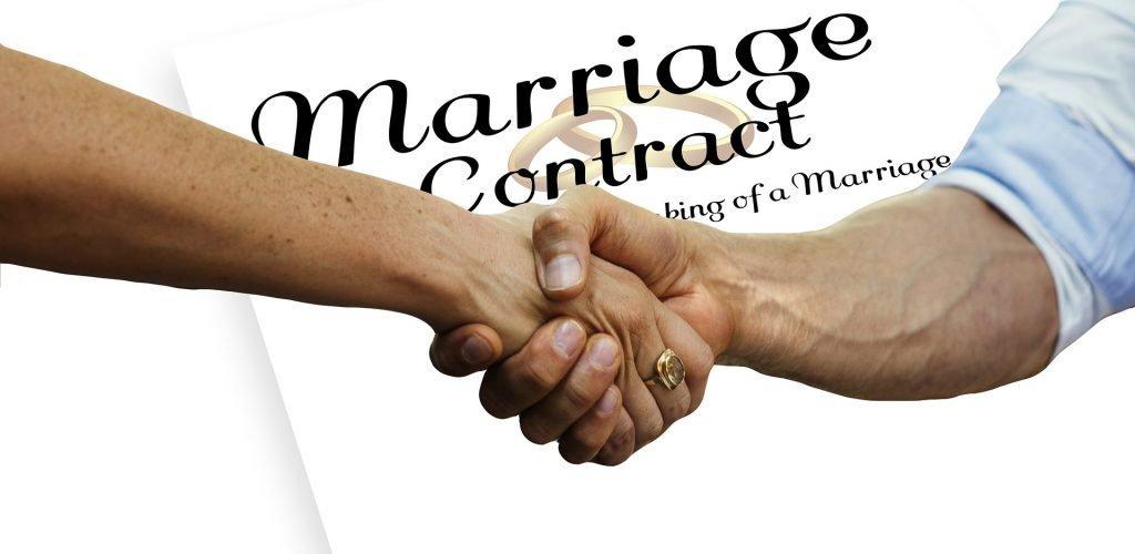 Contratto di matrimonio, mani che si stringono di uomo e donna