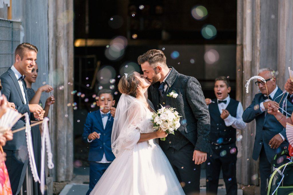 due sposi che si baciano e che hanno preso il congedo matrimoniale