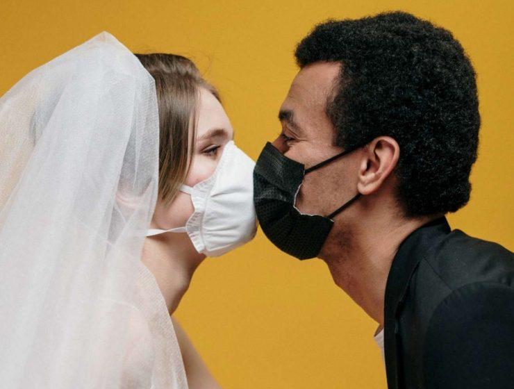 Due sposi si baciano con la mascherina ai tempi del Covid